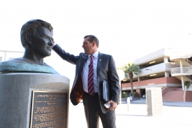 """Heeke pays a visit to the bust of John Byrd """"Button"""" Salmon, the UA student-athlete who coined the motto """"Bear Down."""" (Photo: Stan Liu/Arizona Athletics)"""