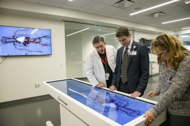 (From left) Allan Hamilton, executive director of the Arizona Simulation Technology and Education Center, Kevin Moynahan, College of Medicine–Tucson deputy dean for education, and Deana Ann Smith, health care simulation educator, work on a life-size virtual dissection table. (Photo by Kris Hanning/Health Sciences)