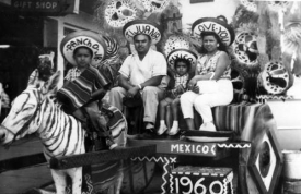 A family sits on a wagon in Tijuana, Mexico, in 1960. The mule that drives the wagon is painted to look like a zebra. All of the individuals in the photograph wear sombreros with different slogans. (Courtesy of Special Collections)
