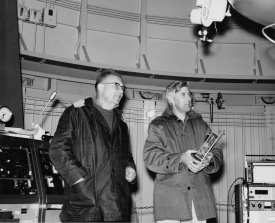 Kuiper and Whitaker holding a 5-by-7-inch lunar camera, preparing to take photographs of the moon in the dome of the 61-inch Catalina Reflecting Telescope – now called the Kuiper 61-inch Telescope – on Mount Bigelow in March 1966. (Photo courtesy of the UA Lunar and Planetary Laboratory)