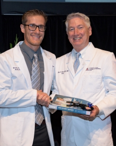 Dr. Guy Reed (right) shakes hands with College of Medicine student Weston Frazier during the school's White Coat Ceremony on July 21. (Photo by Sun Czar Belous, University of Arizona)