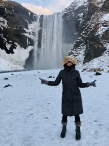 Solange Duhamel, associate professor of molecular and cellular biology, stands in front of one of Iceland's stunning waterfalls.