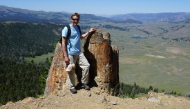 Bryan Black stands next to a petrified tree at Yellowstone National Park.
