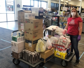 Danielle Oxnam, executive assistant in the Office of University Initiatives, prepares a shipment of personal protective equipment to the Navajo Nation. (Photo courtesy of Alex Robie)