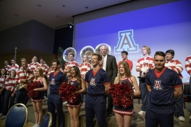 Robbins made opening remarks while standing with members of the UA Pep Band and cheerleading team. (Photo by Kris Hanning/AHS BioCommunications)
