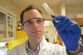 Tad Pace, pictured here with a vial of blood, runs a research lab at the College of Nursing. He will analyze saliva for cortisol to gauge stress levels in See Me Serene study participants. (Image courtesy of the College of Nursing)