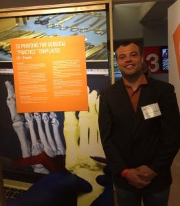 "Dr. Giovinco by a display panel describing his work at ""Design for Social Impact."" (Photo credit: Travis S. Taylor, wanderlustATLANTA.com)"