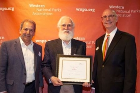 Anthropology professor T.J. Ferguson, center, stands with James E. Cook, right, executive director of the Western National Parks Association, and Ernie Quintana, the chair of the association's board.