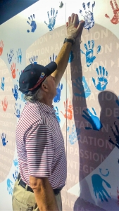 UA President Robert C. Robbins adds his handprint to a mural showing the University's values. (Photo by Drew Bourland/Marketing & Brand Management)