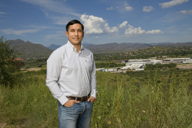 Jose R. Soto, assistant professor in the School of Natural Resources and the Environment, stands along the U.S.-Mexico border overlooking a produce-trucking facility. Soto attended the UA as a first-generation college student, and found his calling studying the economics of humans' interactions with nature. (Photo: Kris Hanning/UAHS BioCommunications)