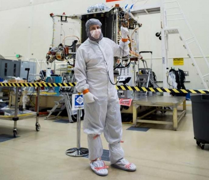 "Bradley Williams, a UA alumnus and project manager at Steward Observatory, stands with the OSIRIS-REx spacecraft in the Lockheed Martin cleanroom. As a 2019 Flinn-Brown Fellow, Williams hopes to find ways to make Arizona's aerospace industry ""a force for progress and change in the state."" (Photo courtesy of Bradley Williams)"