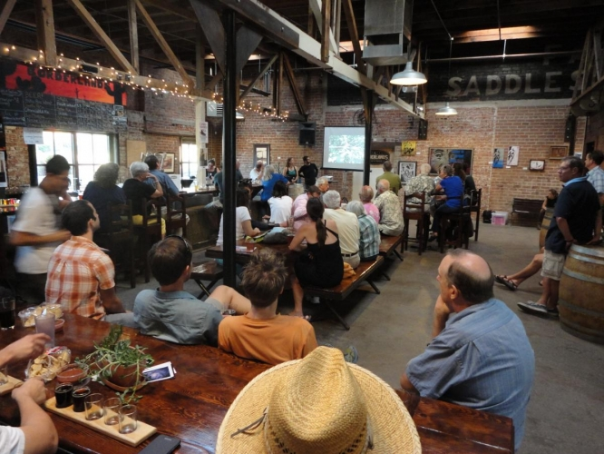 A crowd listens to a Science Café presentation at Borderlands Brewing.