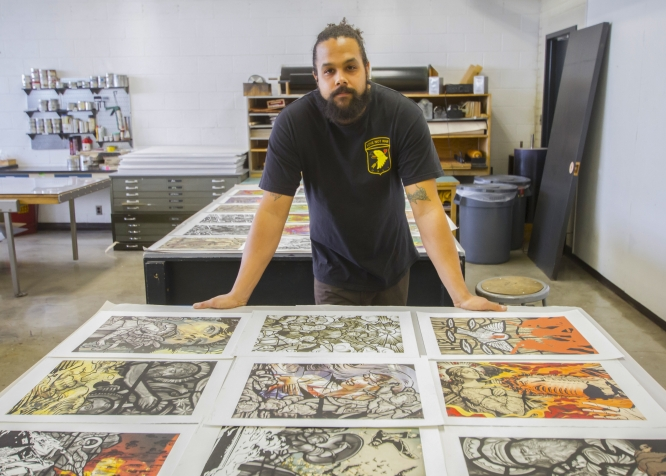 Aaron Coleman with some of his work at the UA School of Art's print shop. (Photo by Kyle Mittan/University Communcations)