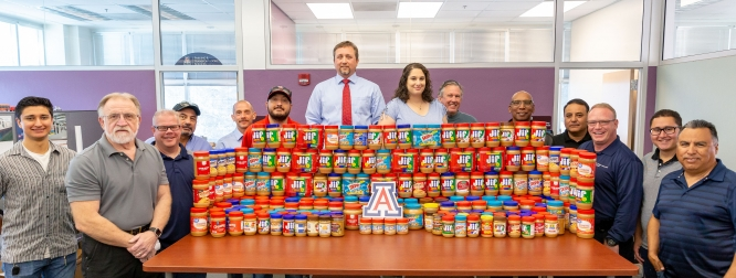 The PTS Enforcement Team with a portion of the 223 donated jars of peanut butter. From left: Juan Carlos Llamas, Steve Mesich, Sean Bailey, Mike Acosta, Don Kitch, Moses Montaño, Elton Crawford, Jenna Aldulaimi, Gary Blanton, Tracy Suitt, Carlos Gonzales, Alan Remick, Manuel Arenas and Al Espinoza. (Photo courtesy of Parking & Transportation Services)