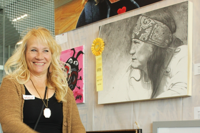 """Jennie Norris, a graphic designer in Facilities Management and professional watercolorist and painter, with her drawing """"Jimmy."""" The piece won Best of Show at """"On Our Own Time"""" in 2018. The exhibit will mark its 10th year when it opens in early February."""