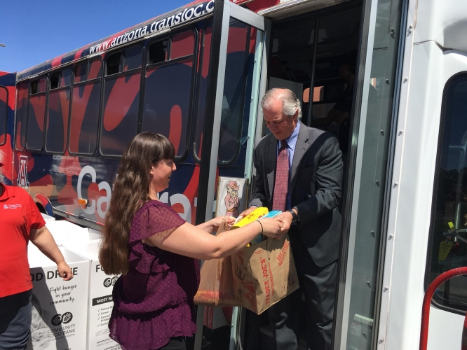 UA President Robert C. Robbins collects a box of food during a previous Stuff the Cat Tran. This year's event will run 7 a.m. to 6 p.m. on April 8.