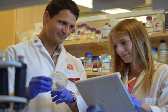 """Brittany Forte (right) works in the lab of Samuel Campos (left), associate professor in the Department of Immunobiology and Cancer Biology Graduate Interdisciplinary Program. Campos says the most rewarding part of his job is helping his students """"overcome obstacles to grow, develop, mature, succeed and advance."""" (Photo: Nicole Swinteck)"""