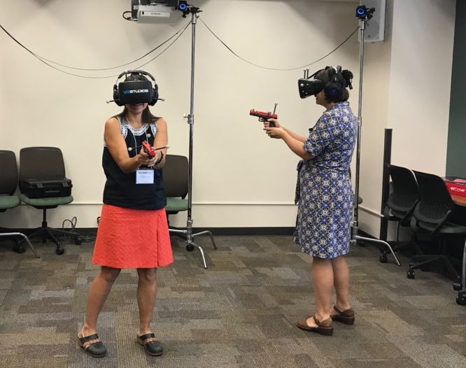 Jennifer Nichols, left, and Cynthia Elliott try out VR. Both are employees of University Libraries. (Photo by Christine Fox, Defense and Security Research Institute)