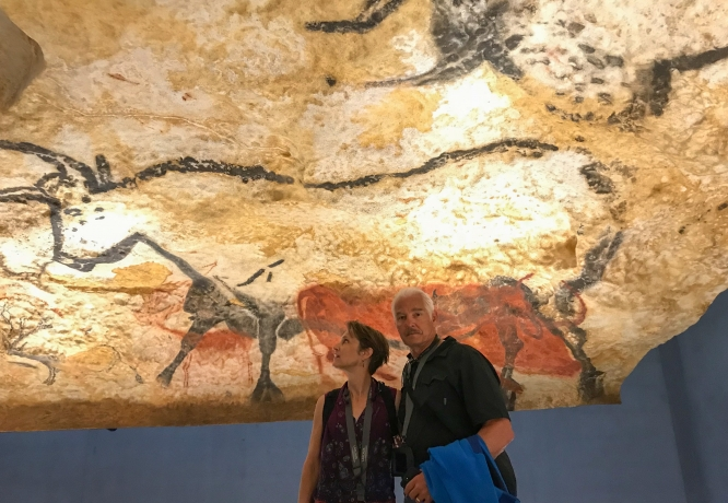 Netzin (left) and Dieter Steklis stand in front of a cave painting of an aurochs in Lascaux, a cave complex in southern France. The aurochs, a prehistoric ancestor of the cow, is the only animal that prehistoric people painted life-size. (Photo courtesy of Dieter Steklis)