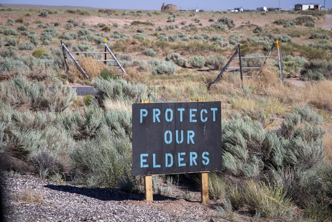 University researchers say a high level of cultural competence can help scientists and health care providers address disparities faced by underrepresented communities. This photo shows a sign on the Navajo Nation reminding people to wear masks to protect older residents.