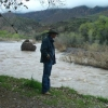 Dick Kaler watches storm runoff erode a section of the San Francisco River running through his ranch in eastern Arizona.