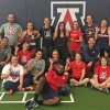 A group of 15 employees in workout gear gather in an athletics facility.