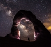 A person wearing a headlamp under a rock arch, looking up at a starry sky