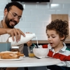 A man eats breakfast with his son at a kitchen table